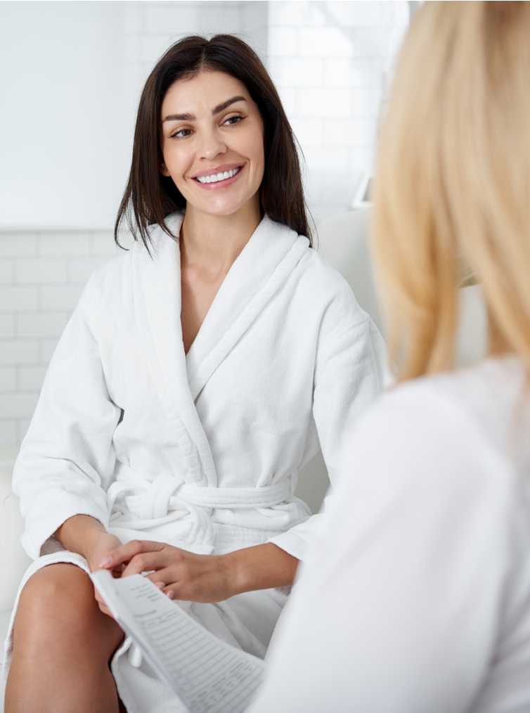 woman in spa robe smiling at a consultation with doctor