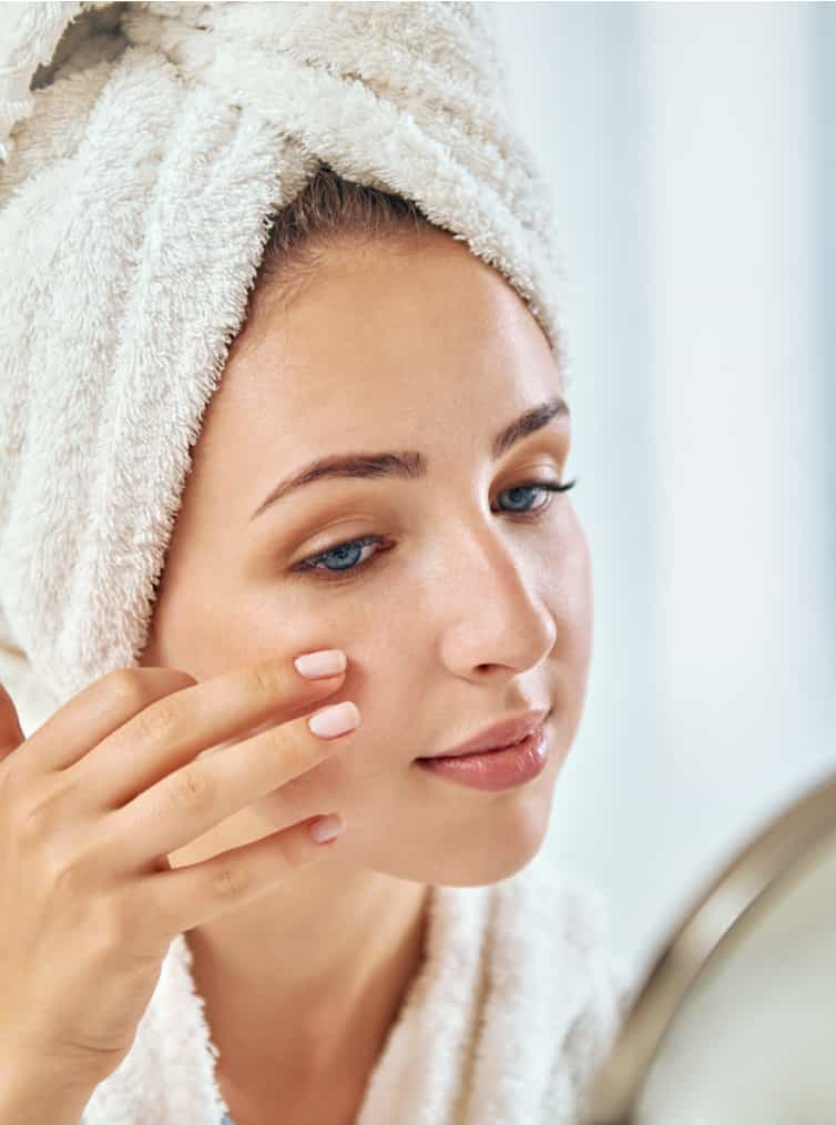 beautiful woman examining face after facial treatment