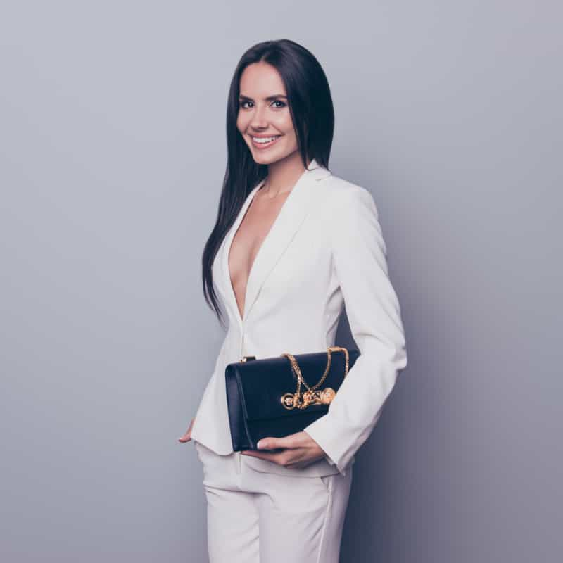 Rich business woman smiling with expensive purse and business suit