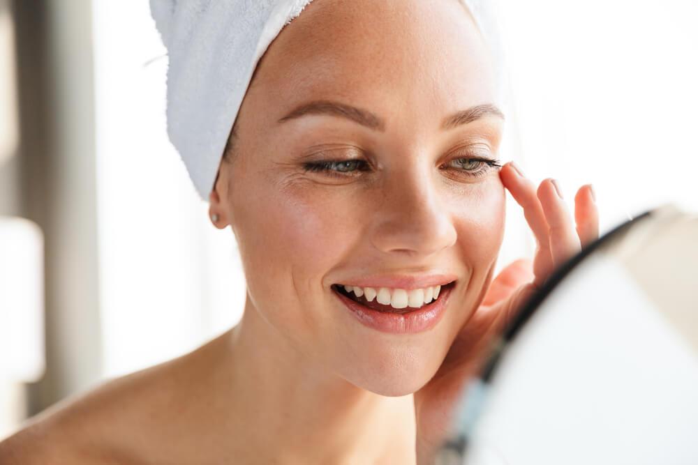 woman examining skin in mirror