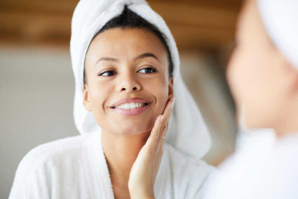 woman examining skin in the mirror