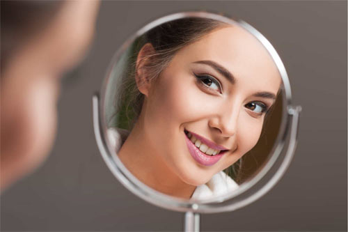 woman staring in mirror smiling